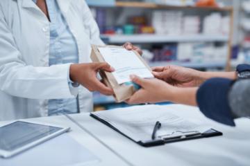 Pharmacist hands prescription pharmaceuticals to patient.