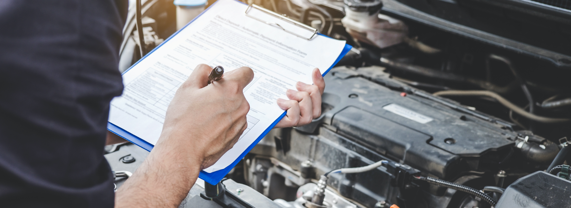 Mechanic inspects car with clipboard to note possible defects.