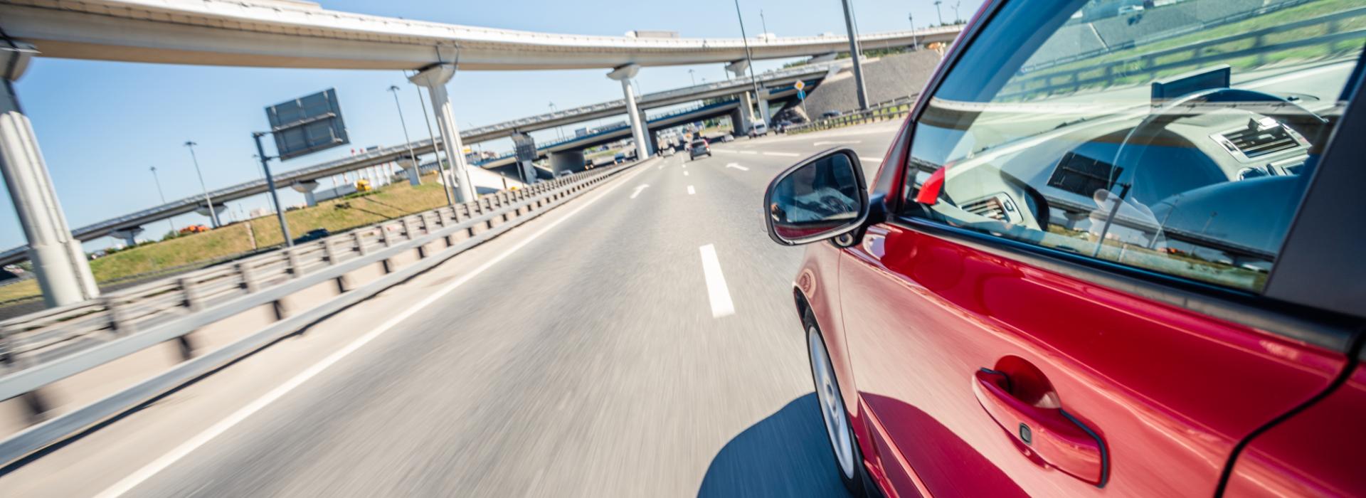 Red car speeding down the highway.