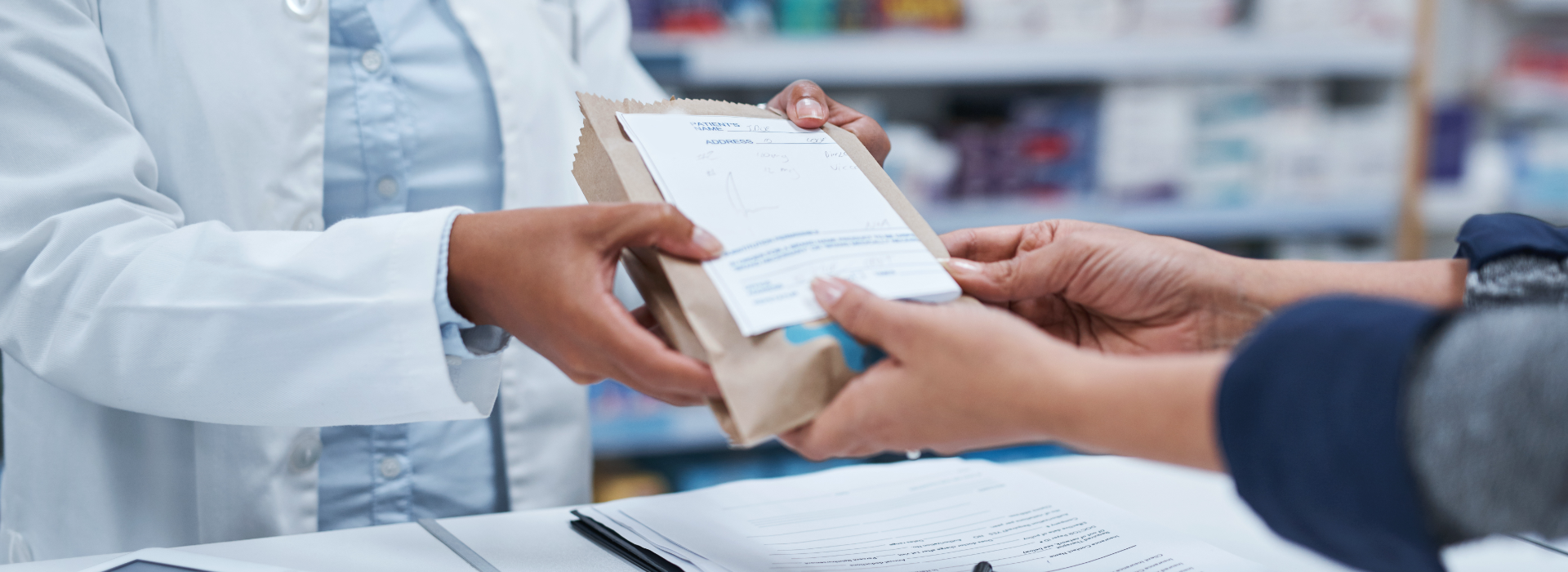 Pharmacist hands prescription pharmaceuticals to patient.