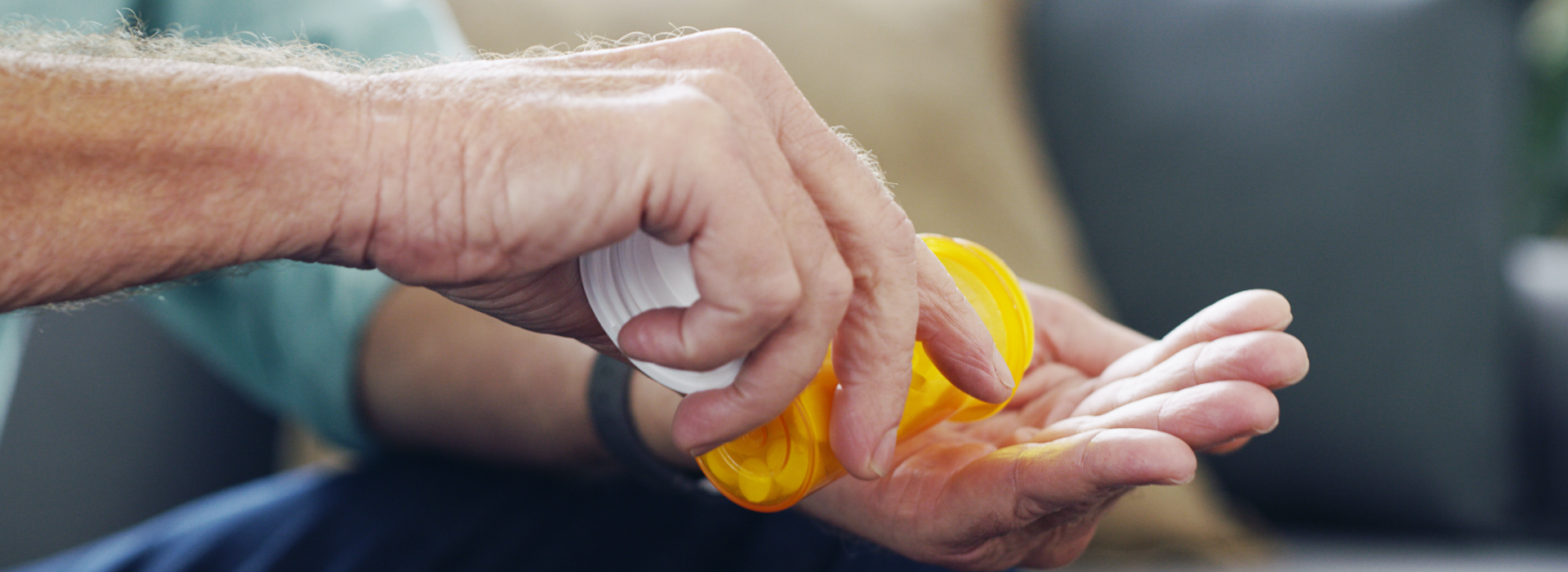 Man holds hand out while pouring medication from prescription bottle.