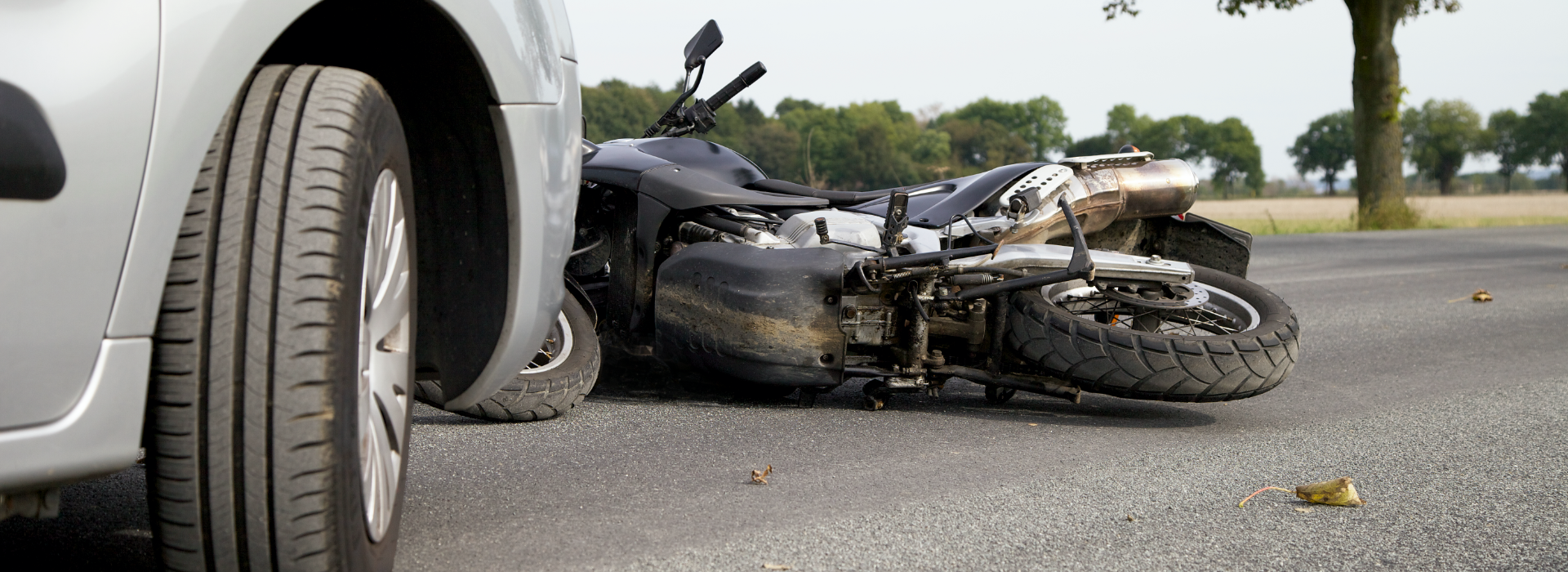 Motorcycle likes on ground after car crashes into it.