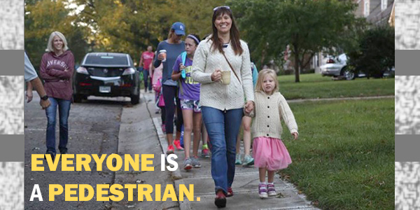 "Parents walking on sidewalk with children and text reading ""everyone is a pedestrian"""