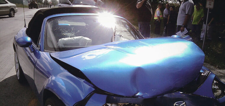 Blue convertible mangled after car crash.