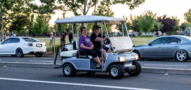 Two people driving a golf cart down a public street