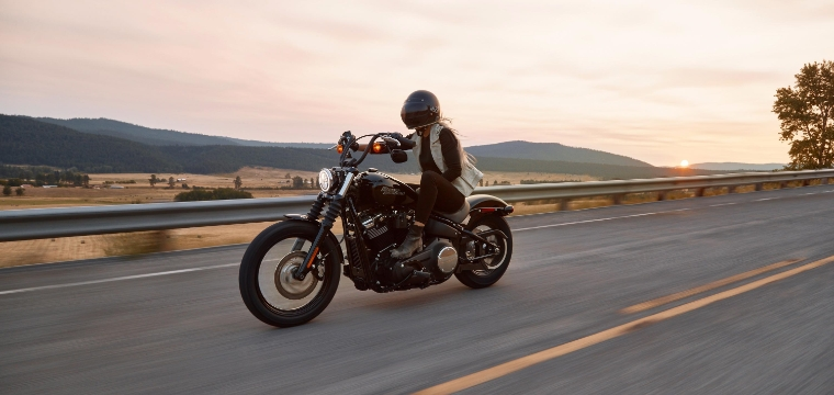 Motorcyclist riding down a two lane road at sunrise, practicing summer motorcycle safety