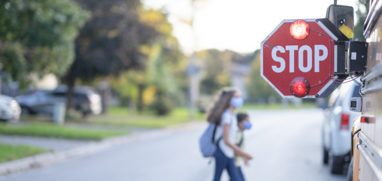 Children step onto a school bus with the stop sign out for back to school safety