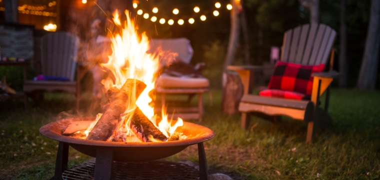 A campfire is burning in a backyard fire pit, with lawn chairs and lights in the background.