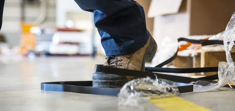 Person wearing a boot and blue jeans tangled up in packaging materials right before a workplace injury